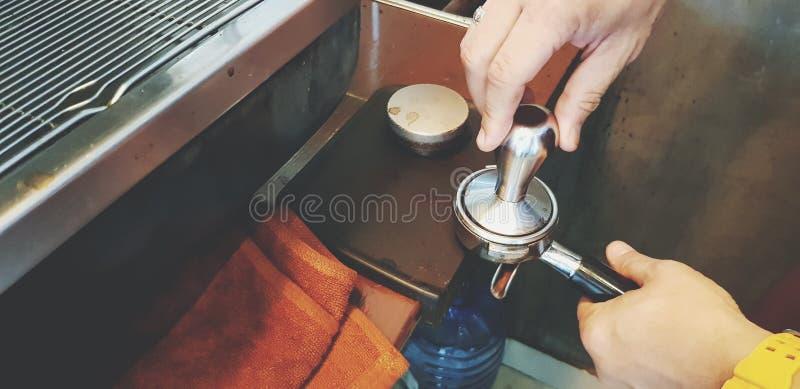 Abschluss herauf die Hand der baristas unter Verwendung des Besetzerwerkzeugs und -schleifers, zum des Espressoschusses zu machen stockbild