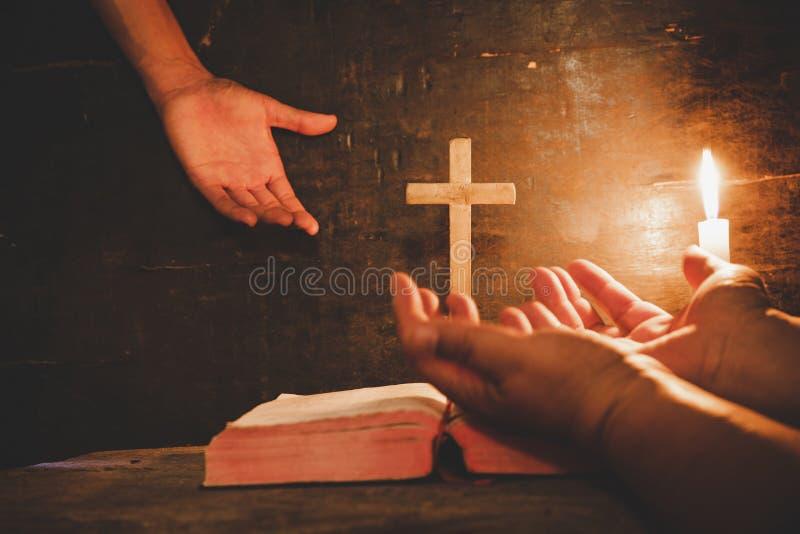Abschluss herauf die Hand des Mannes betet in der Kirche mit brennender Kerze stockbilder