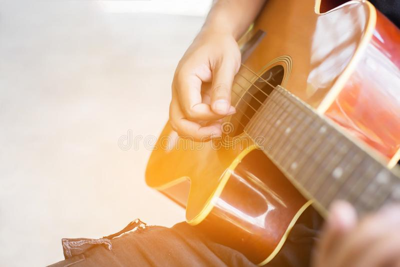 Abschluss herauf die Hand des Mannes, welche die Gitarre spielt lizenzfreies stockbild