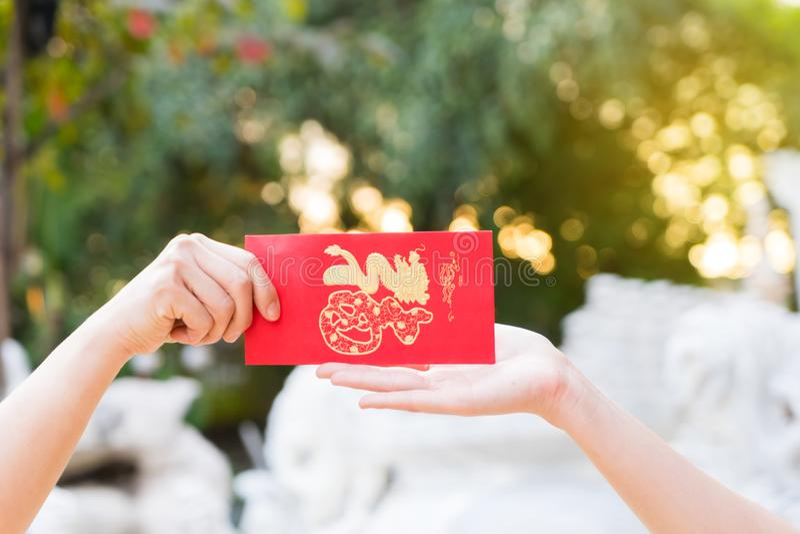 Abschluss herauf die Hand, die gedenkwürdig hält, rote Umschlag Symbole des Chinesischen Neujahrsfests auf goldenem bokeh Hinterg lizenzfreie stockfotos