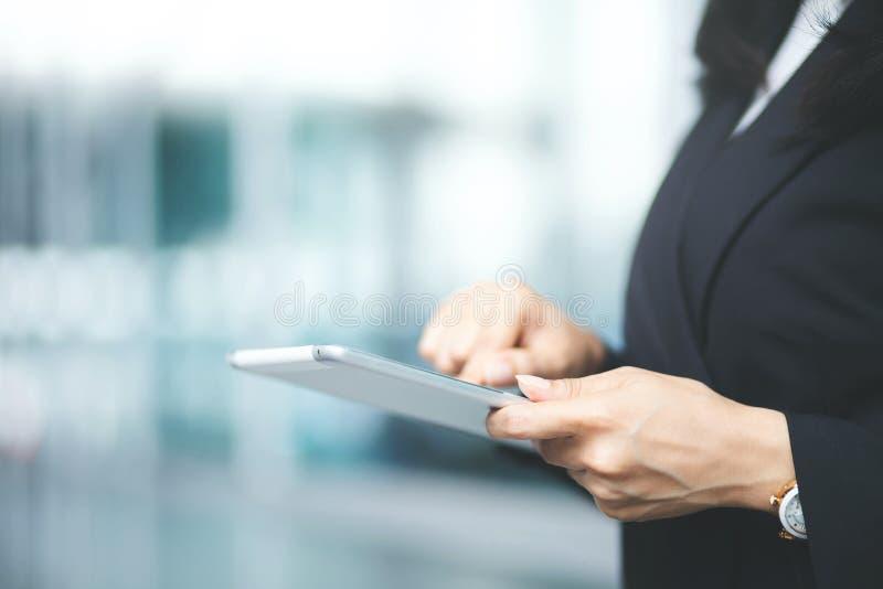 Abschluss herauf die Handgeschäftsfrau, die unter Verwendung eines digitalen Tabletten-PC-Gerätes bei der Stellung in der Front a stockbild
