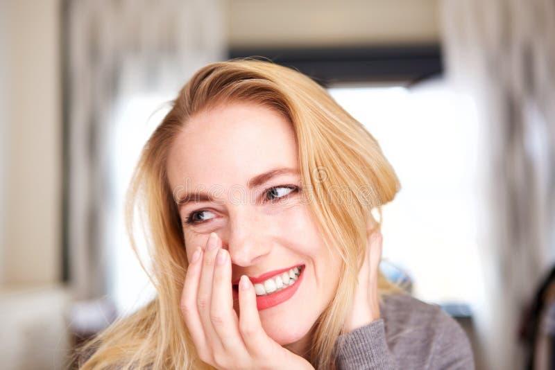 Abschluss herauf die junge blonde Frau, die zu Hause lacht stockbilder