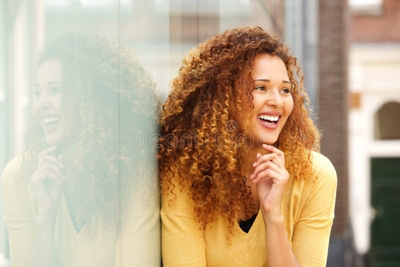 Abschluss herauf die junge Frau, die draußen in der Stadt lacht stockbild