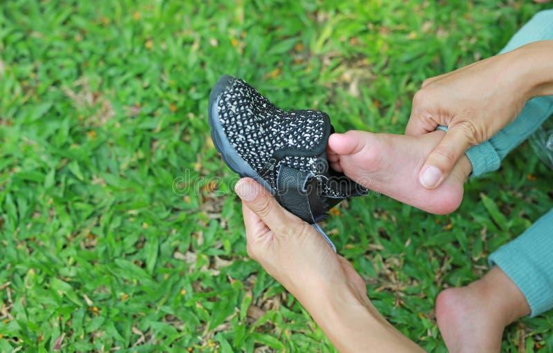 Abschluss herauf die Mutterhände, die kleine Schuhe ihrem Sohn in den grünen Rasen vorlegen lizenzfreies stockfoto