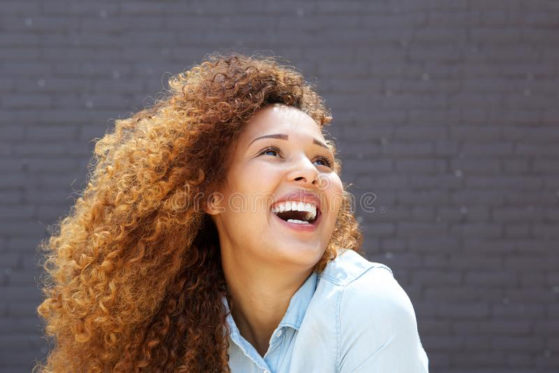 Abschluss herauf die schöne junge Frau mit dem gelockten Haar oben lächelnd und schauend stockbild