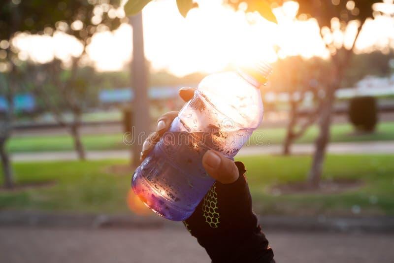 Abschluss herauf die sportliche Frauenhand, die Mineralwasser mit Sonnenunterganglicht hält lizenzfreies stockfoto