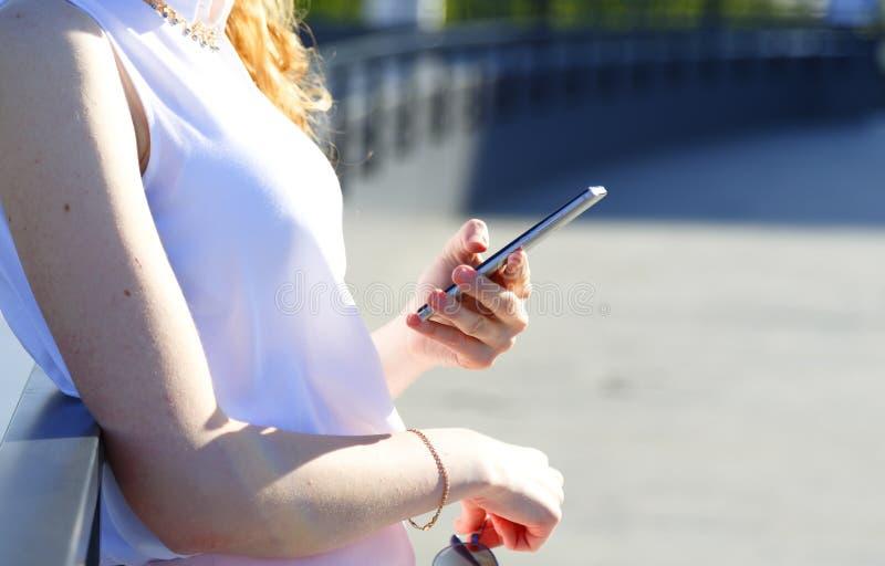 Abschluss herauf die weibliche Hand, die Telefon hält und Mitteilung in der Stadtstraße schreibt stockbilder