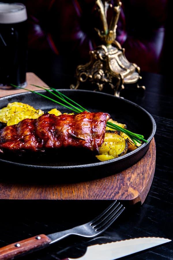 Abschluss herauf feinschmeckerisches Hauptgericht mit gegrillter Schweinefleisch-Rippe und Fried Potatoes auf schwarzer Wanne Ged lizenzfreie stockbilder