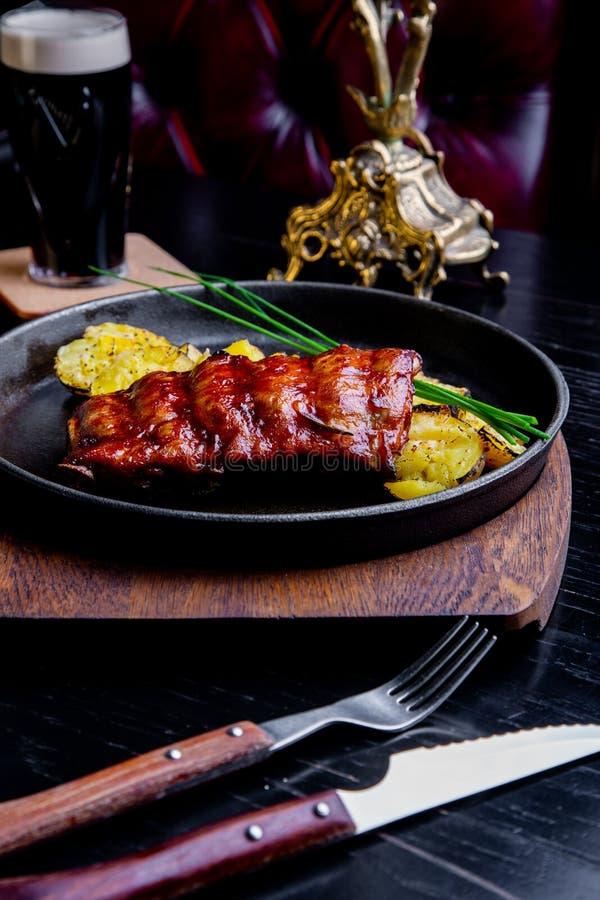 Abschluss herauf feinschmeckerisches Hauptgericht mit gegrillter Schweinefleisch-Rippe und Fried Potatoes auf schwarzer Wanne Ged stockbilder