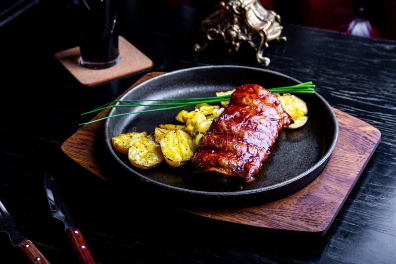 Abschluss herauf feinschmeckerisches Hauptgericht mit gegrillter Schweinefleisch-Rippe und Fried Potatoes auf schwarzer Wanne Ged stockfoto