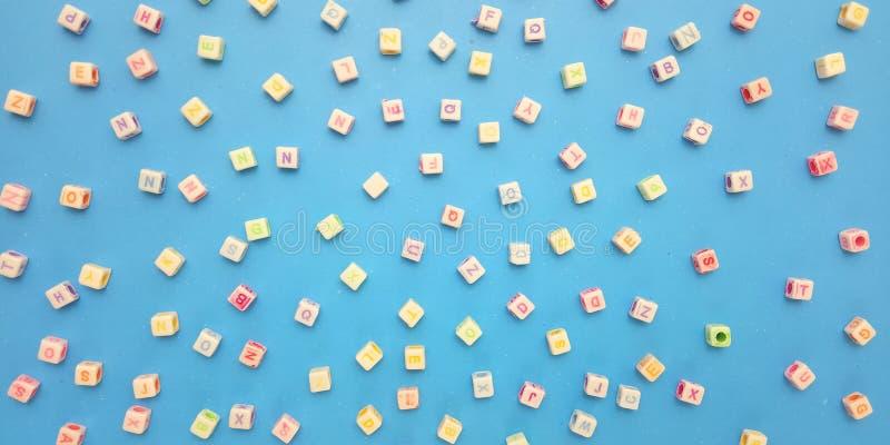 Abschluss herauf flache Lage, blauen Hintergrund und Alphabet-Plastikw?rfel-Perlen-Element-Entwurf f?r Mitteilung, Zitat, Informa stockfotos