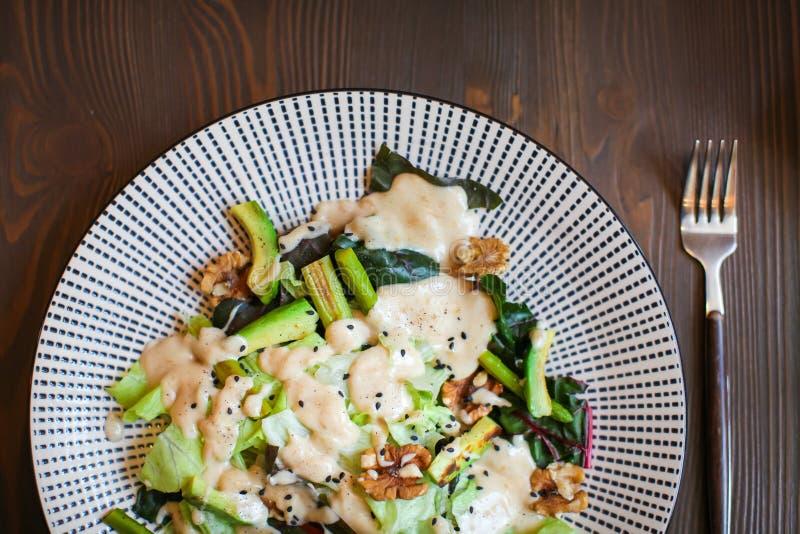 Abschluss herauf gesunden Salat mit Avocado, Walnüssen und gegrilltem Spargel Nahrung des strengen Vegetariers auf dunklem Holzti stockfotos