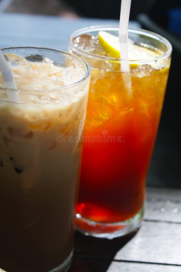 Abschluss herauf Glas Zitronentee und Milchkaffee Und Eis gelegen auf dem Holztisch lizenzfreies stockbild