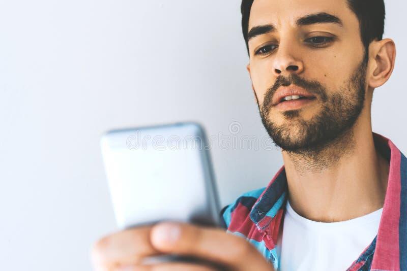 Abschluss herauf hübschen kaukasischen Mann im Hemd unter Verwendung des Handys, den Schirm mit ernstem und starkem Ausdruck betr lizenzfreies stockbild