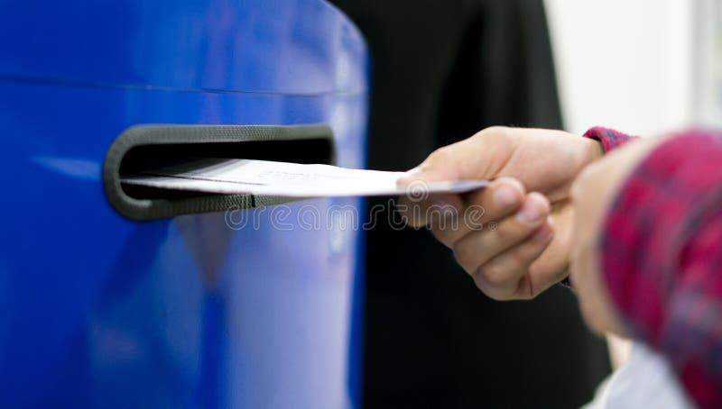 Abschluss herauf Handtropfenbuchstaben und Dokumente im blauen Postbox in Postpost f stockfotografie