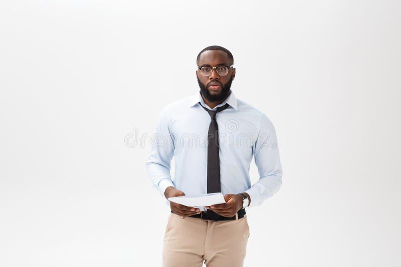 Abschluss herauf jungen afro-amerikanischen Geschäftsmann mit dem Betrachten der Kamera beim Halten des Dokumentenpapiers lizenzfreie stockfotos