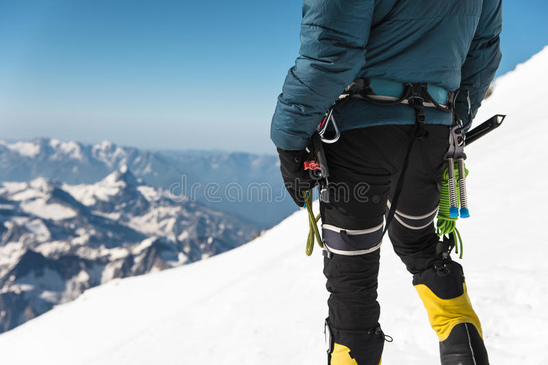 Abschluss herauf jungen Kerlbergsteiger A hält in seiner Hand eine Eisaxt, die auf einem Gipfel steht, der in den Bergen hoch ist stockfotografie