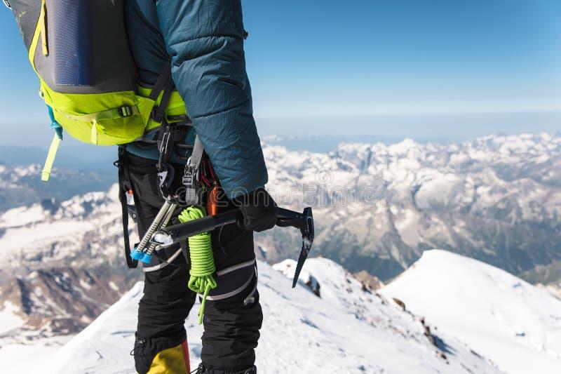 Abschluss herauf jungen Kerlbergsteiger A hält in seiner Hand eine Eisaxt, die auf einem Gipfel steht, der in den Bergen hoch ist lizenzfreie stockfotografie