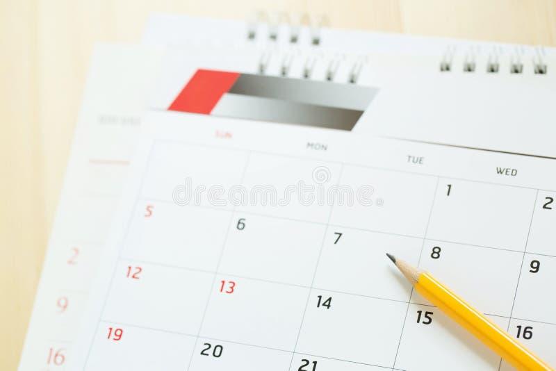 Abschluss herauf KalenderSeitenzahl Bleistift gelb den Wunschtermin markieren, um Gedächtnis auf dem Tisch zu erinnern lizenzfreie stockfotografie