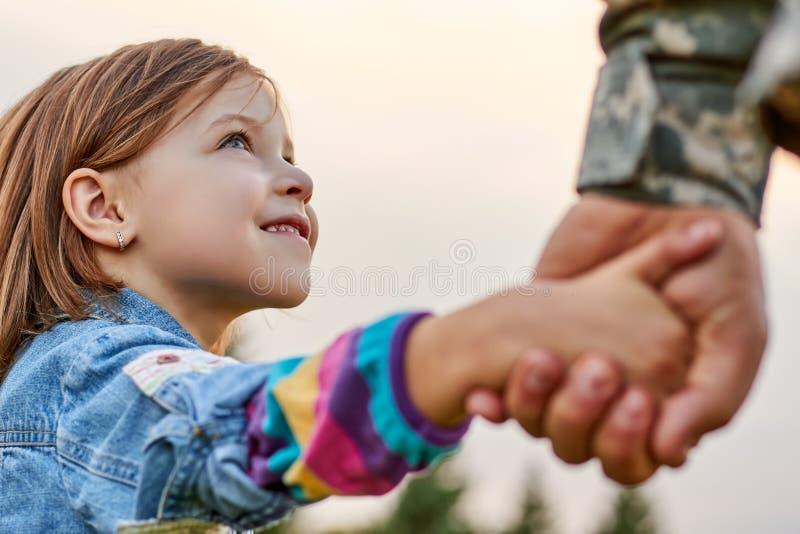 Abschluss herauf kleines Mädchen des Porträts betrachtet seinen Militärvater lizenzfreie stockfotos