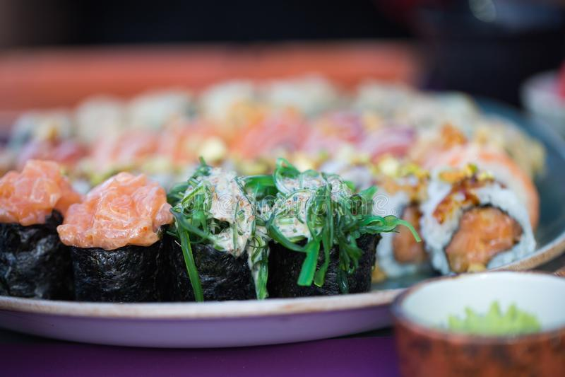Abschluss herauf Lebensmittelbild des Sushisatzes diente auf keramischem Plattenhintergrund Foto für Text und Gestaltungselemente lizenzfreie stockfotografie