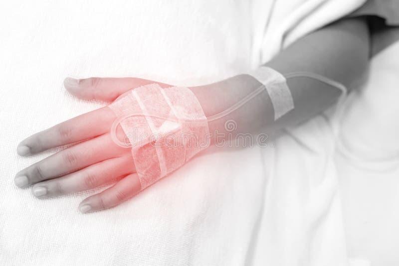 Abschluss herauf Leutefokus auf der Hand eines geduldigen Kranken auf dem Bett stockbild
