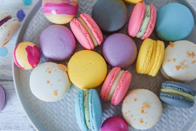 Abschluss herauf mehrfarbige franz?sische macaron Kuchen auf blauer Platte und wei?em h?lzernem Hintergrund Weiß, gelb, Rosa, Pur lizenzfreie stockfotografie