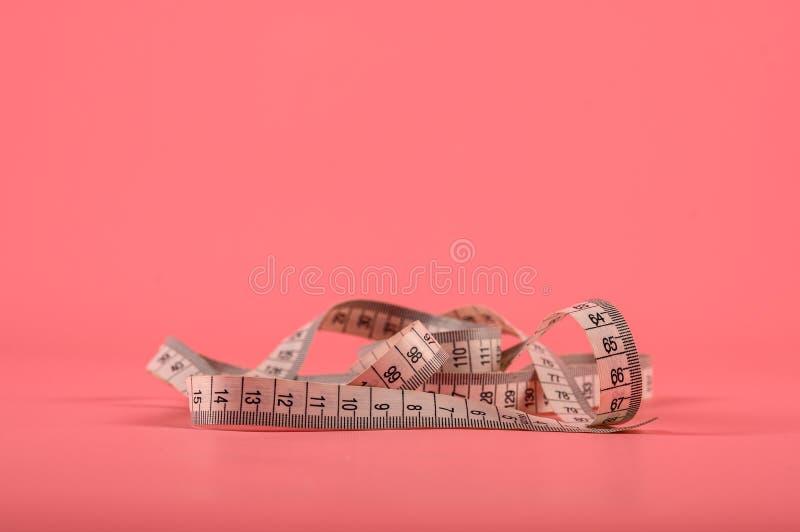 Abschluss herauf messendes Band des Schneiders auf rosa Hintergrund Grüne messende flache Schärfentiefe des Bands lizenzfreie stockfotografie