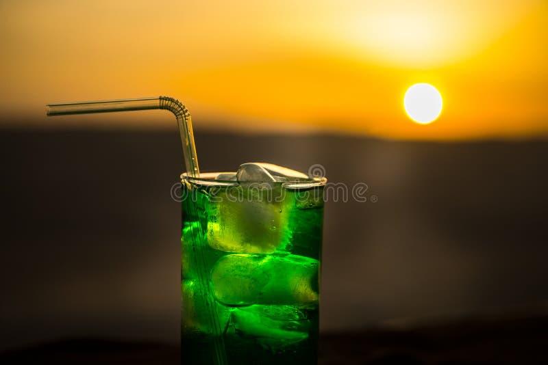 Abschluss herauf nass Glas des grünen kalten tadellosen Getränks, bunter orange Sonnenunterganghintergrund auf der Terrasse Abk?h lizenzfreies stockfoto