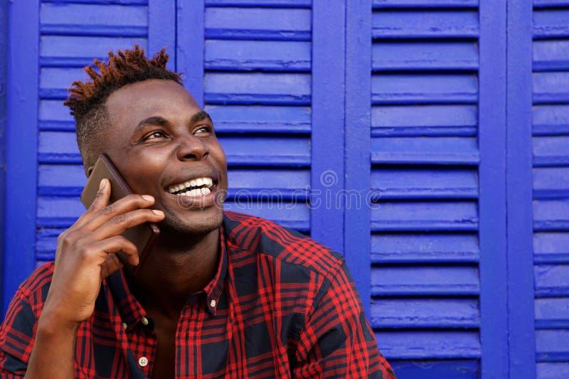 Abschluss herauf netten Afroamerikaner kann am Handy weg sprechen und schauen bemannen lizenzfreie stockbilder