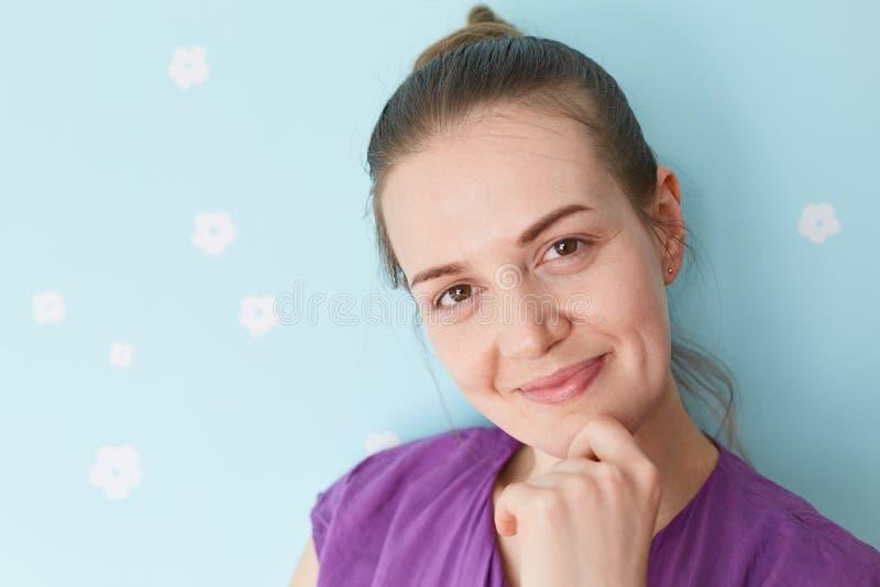 Abschluss herauf Porträt der recht begeisterten jungen Frau hält Kinn, betrachtet positiv Kamera, genießt, Wochenende, kleiden zu stockfotos