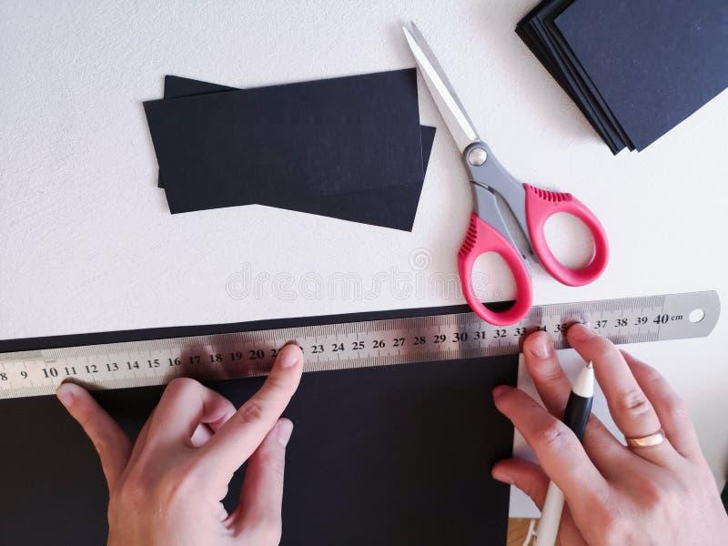Abschluss herauf Schuss - Berufsfrauendekorateur, Designer, der mit Kraftpapier arbeitet und Umschlag an der Werkstatt, Studio ma lizenzfreies stockbild