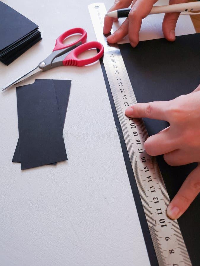 Abschluss herauf Schuss - Berufsfrauendekorateur, Designer, der mit Kraftpapier arbeitet und Umschlag an der Werkstatt, Studio ma stockfotos