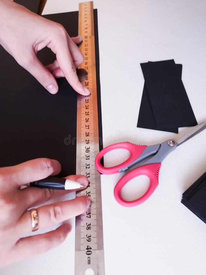 Abschluss herauf Schuss - Berufsfrauendekorateur, Designer, der mit Kraftpapier arbeitet und Umschlag an der Werkstatt, Studio ma lizenzfreies stockfoto