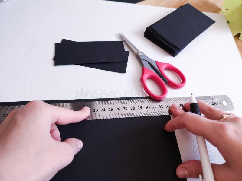 Abschluss herauf Schuss - Berufsfrauendekorateur, Designer, der mit Kraftpapier arbeitet und Umschlag an der Werkstatt, Studio ma lizenzfreie stockfotos