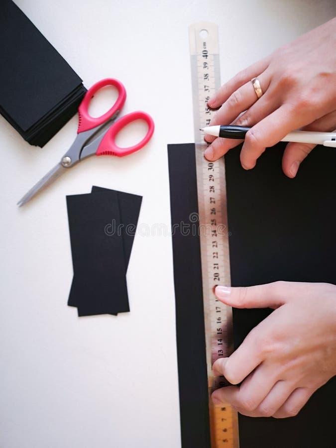 Abschluss herauf Schuss - Berufsfrauendekorateur, Designer, der mit Kraftpapier arbeitet und Umschlag an der Werkstatt, Studio ma stockfoto