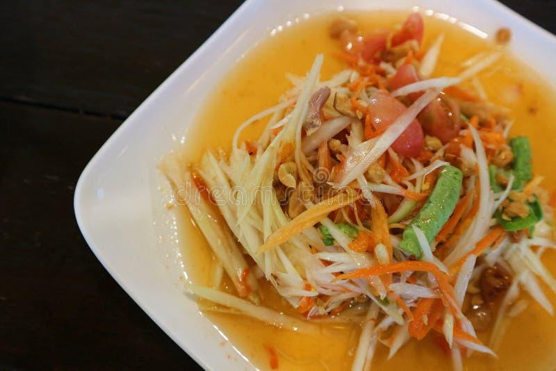 Abschluss herauf würzigen Salat der thailändischen Papaya oder Som Tum in der weißen Platte und im schwarzen Hintergrund lizenzfreie stockbilder