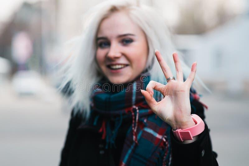 Abschluss im Freien herauf Porträt des jungen schönen glücklichen lächelnden Mädchens, das okaygeste zeigt Vorbildliches Looking  lizenzfreies stockfoto