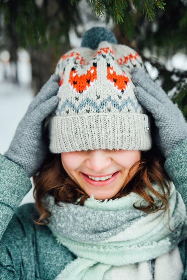 Abschluss im Freien herauf Porträt des jungen schönen glücklichen Mädchens, tragender stilvoller gestrickter Winterhut lizenzfreie stockfotografie
