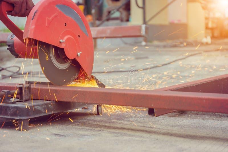 Abschluss oben der Flamme funkt mit elektrischer Werkzeugmaschine des Schleifers für den Schnitt des Stahlrohres in der Werkstatt stockfoto