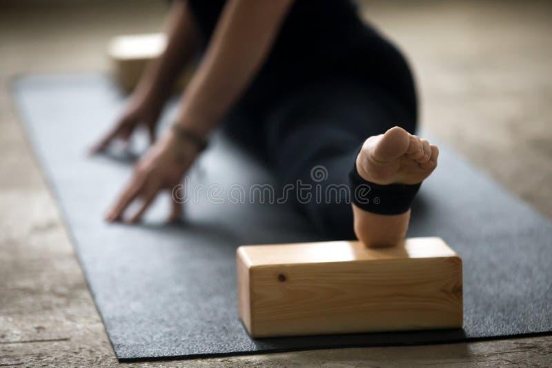 Abschluss oben der Frau, die Spalten mit Block für tiefe Ausdehnung tut stockfoto