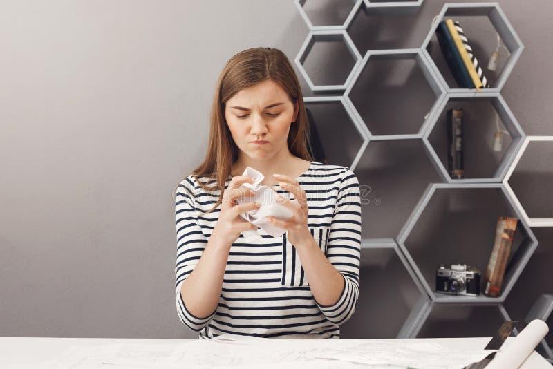 Abschluss oben des frustrierten schönen europäischen dunkelhaarigen weiblichen freiberuflich tätigen Designers zerknittert Papier stockfotos