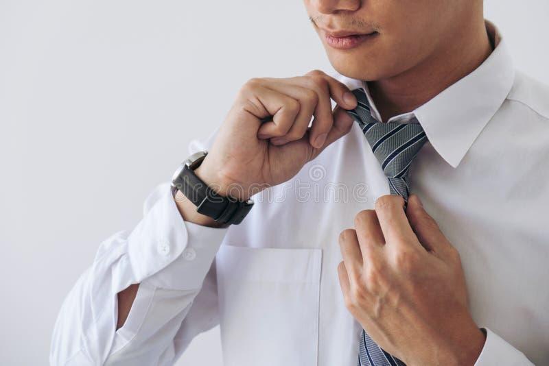 Abschluss oben des jungen attraktiven Geschäftsmannes trägt eine graue Bindung und eine Anzeige lizenzfreies stockbild