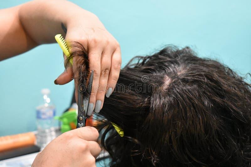 Abschluss oben des jungen Mannes, der einen Haar-Schnitt erhält lizenzfreie stockfotos