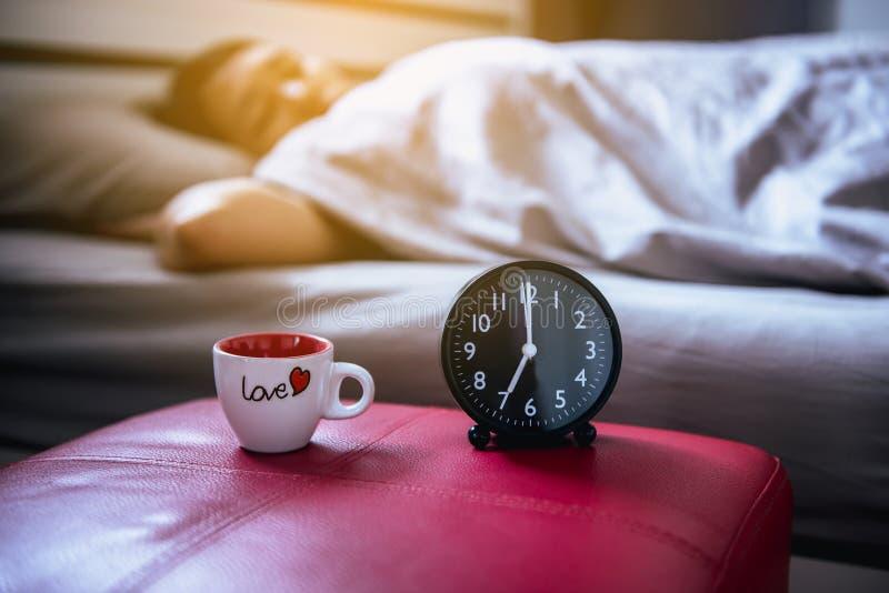 Abschluss oben des Weckers mit der Frau, die auf Bettunschärfehintergrund schläft lizenzfreie stockbilder