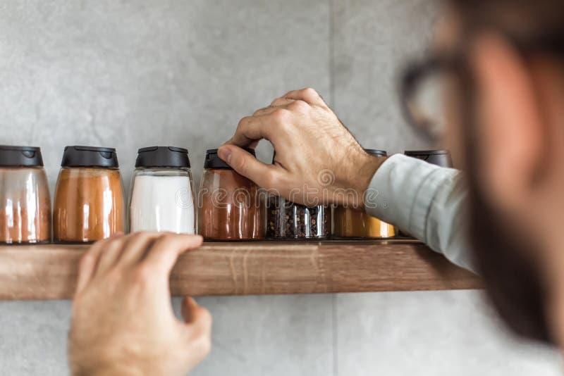 Abschluss oben ein Mann nimmt Gewürze vom Küchenregal stockbild