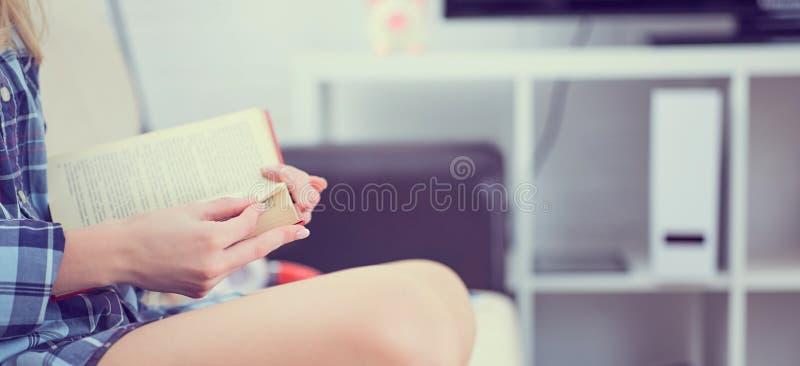 Abschluss- oben eines Buches in den Händen eines Mädchens, das auf der Couch auf Hauptinnenhintergrund sitzt stockbilder