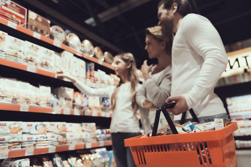 Abschluss oben Familie in Supermarkt-kaufenden Plätzchen lizenzfreies stockfoto