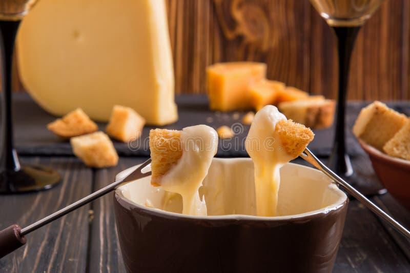 Abschluss oben Feinschmeckerisches Schweizer Fondue-Essen an einem Winterabend mit sortierten Käsen auf einem Brett neben einem e lizenzfreie stockfotos