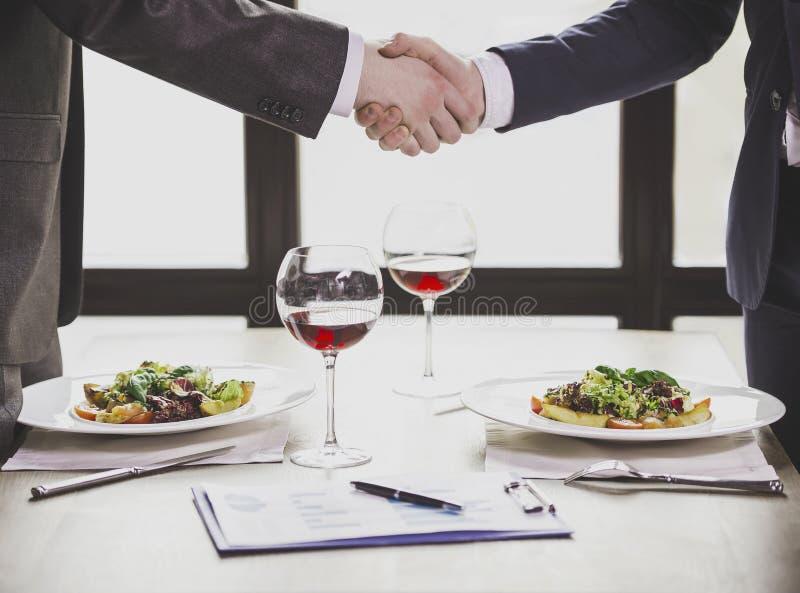 Abschluss oben Geschäftsmänner, die Hände im Restaurant rütteln stockfoto